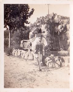 Macia Vilà, amb una bicicleta al costat d'una cascada que hi havia al darrere de la masia de can Cortada, lloc per on avui passa una autopista. Anys 40.